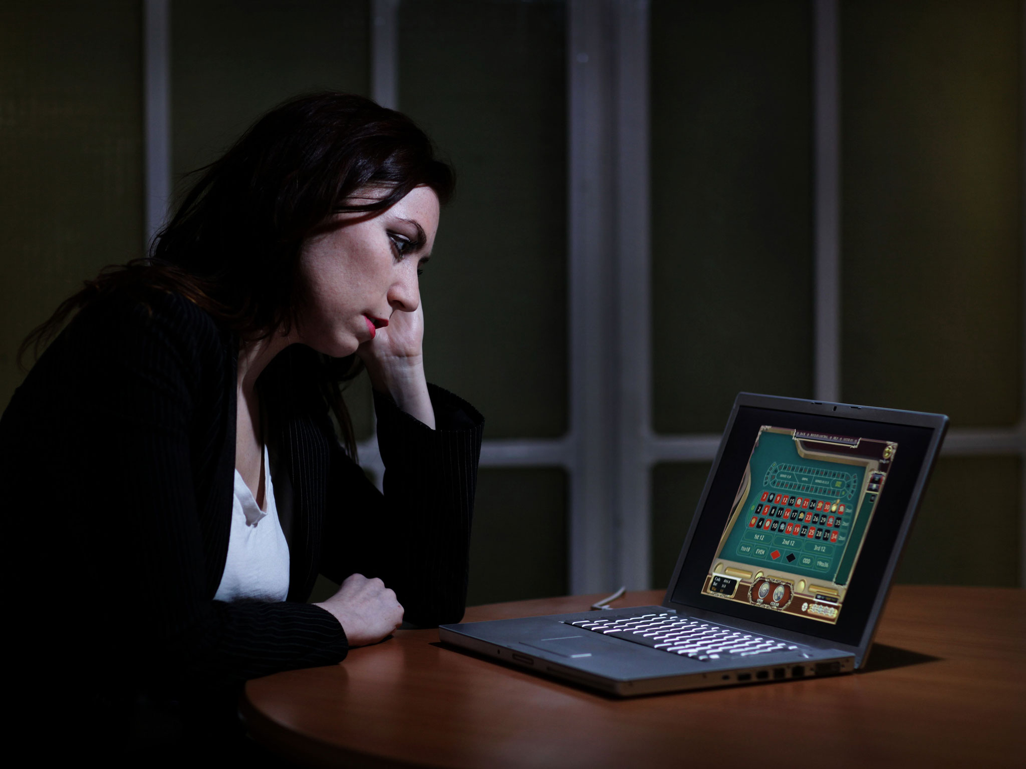 Woman gambling on laptop online at a table