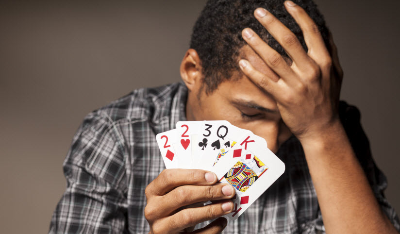 Man with gambling addiction holding cards