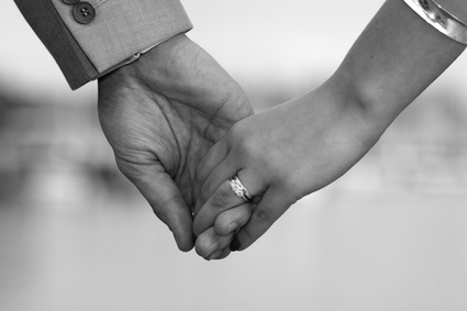 Couple holding hands with wedding ring