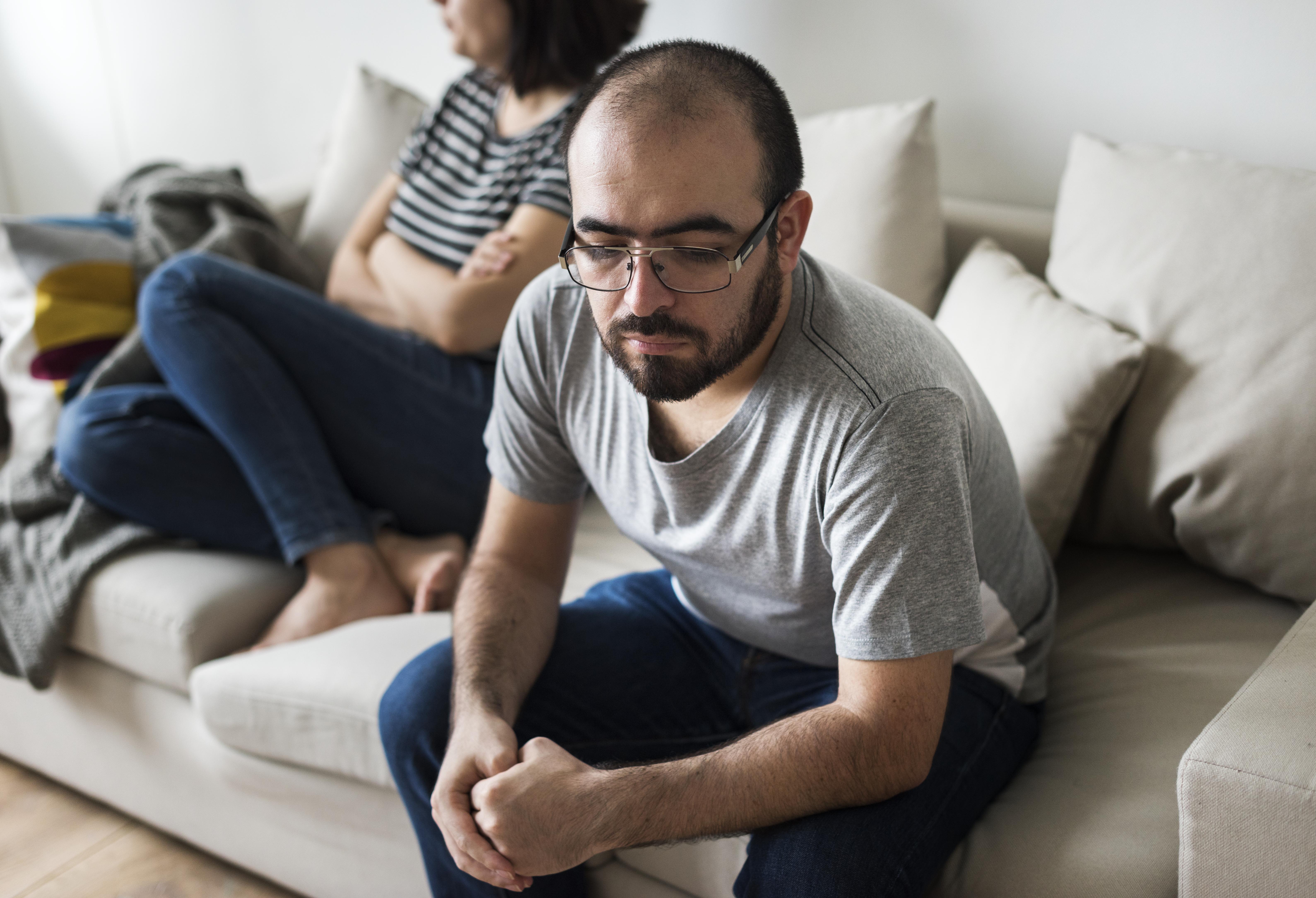 Unhappy couple arguing on the sofa